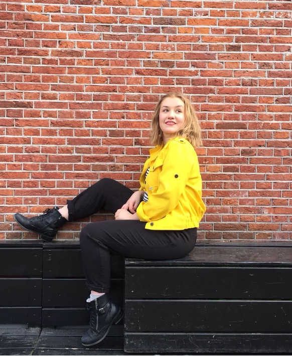 A woman with a yellow jacket sitting on a bench.